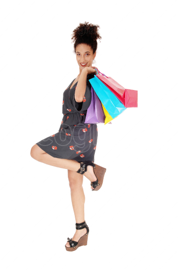 Happy young woman shopping with the bags over her shoulder