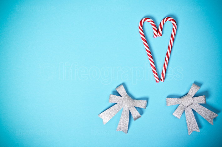 Heart shaped candy canes and bows on pastel blue background
