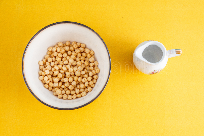 Honey balls of different cereals in a deep bowl and milk on a ye
