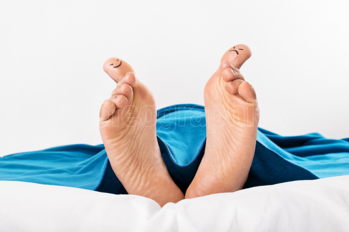Human feet with smiley and grumpy drawn on them