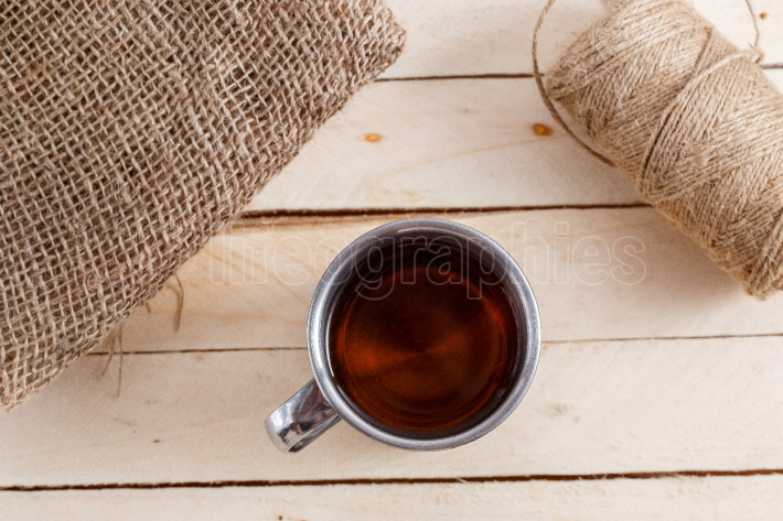 Iron vintage mug with tea on wooden background  next to the tea