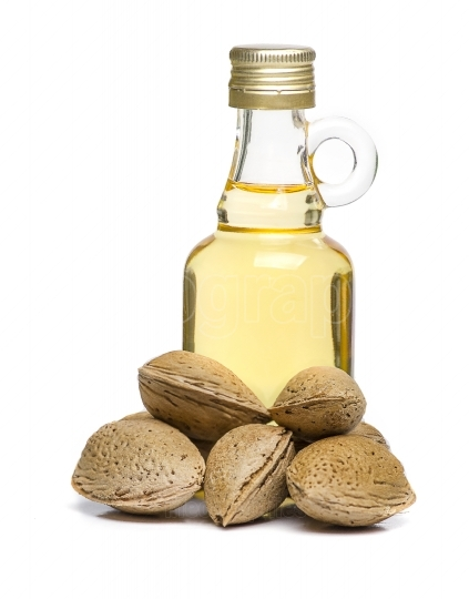 Isolated Almonds oil in a glass bottle with some almonds