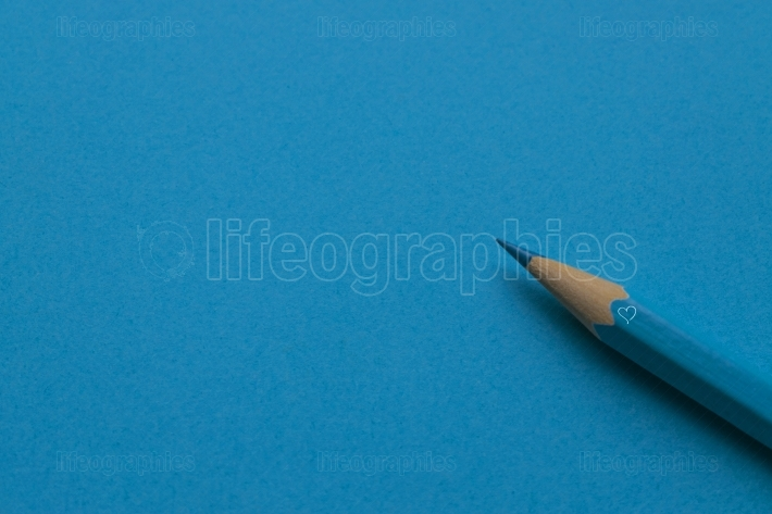 Isolated blue pencil on blue paper