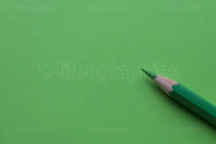 Isolated green pencil on green paper