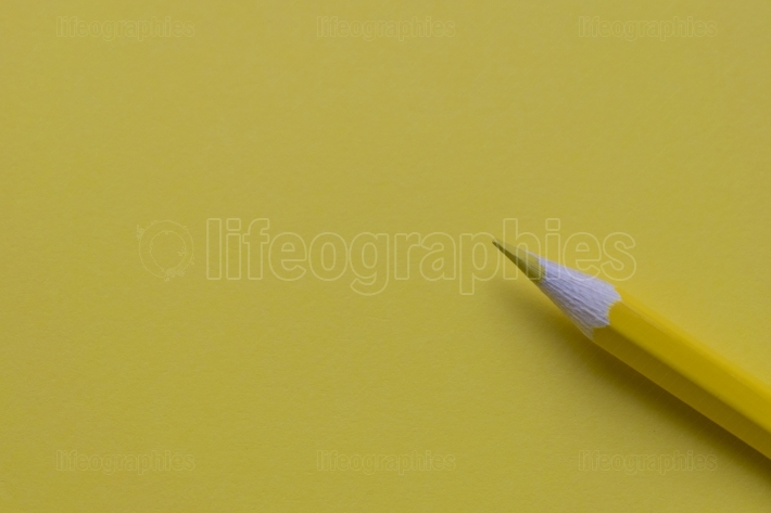 Isolated yellow pencil on yellow paper
