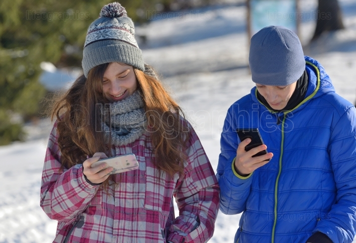 Kids with Smartphone in winter forest