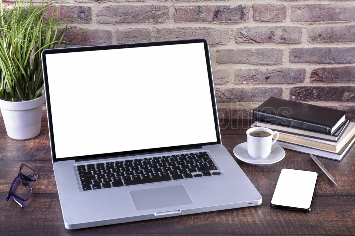 Laptop notebook with blank screen and cup of coffee and notepad