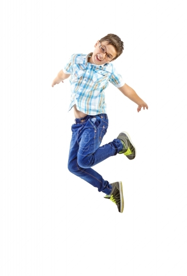 Little boy with glasses jumping on white