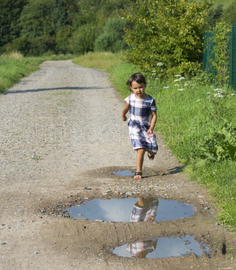 Little child having fun by running and jumping the puddle