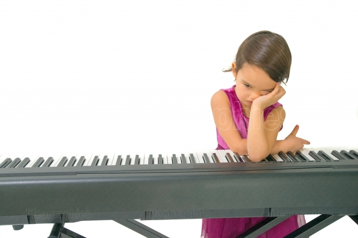 Little girl being tired while practising the piano