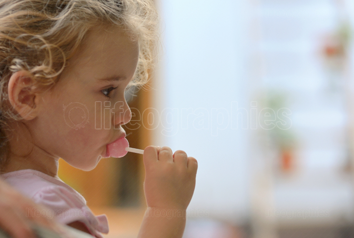 Little girl eating a lolly pop
