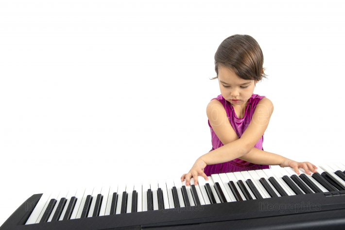 Little girl playing piano isolated on white