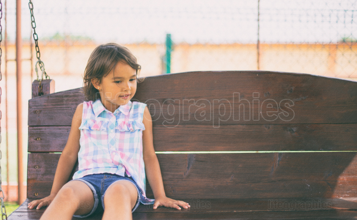 Little girl sitting on bench in the park at the day time
