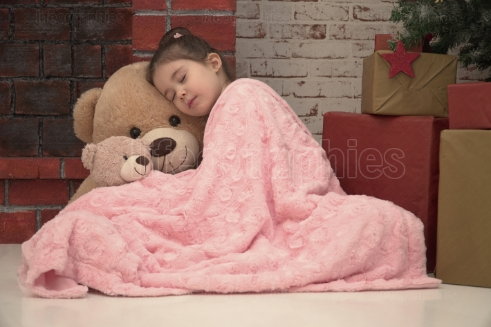 Little girl sleeping with huge plush bear on the floor waiting for Santa