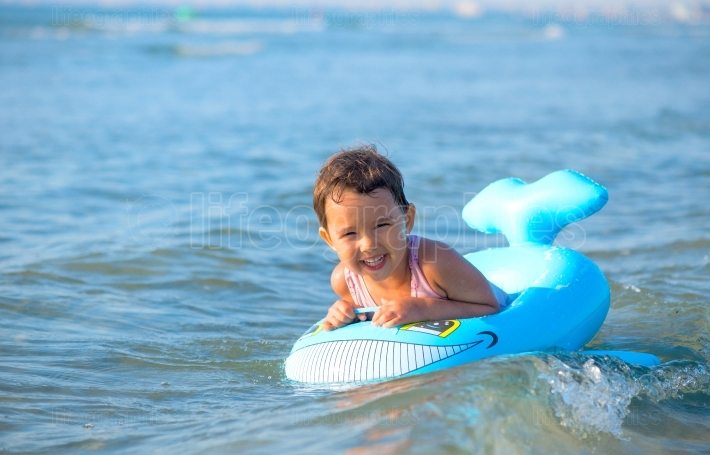 Little girl swimming on inflatable at the sea