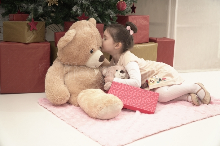 Little girl with her teddy bear friend on Christmas Eve