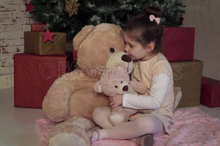 Little girl with two different sizes toy bears waiting for Santa on Christmas Eve