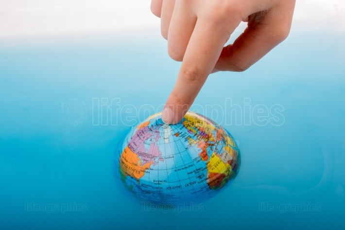 Little globe  with finger on top floating