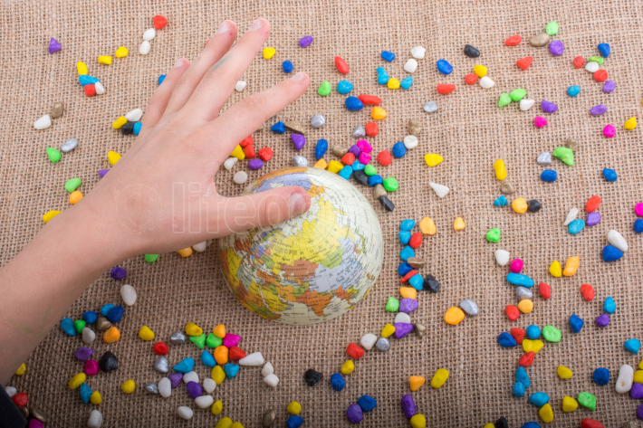 Little model globe amid colorful pebbles
