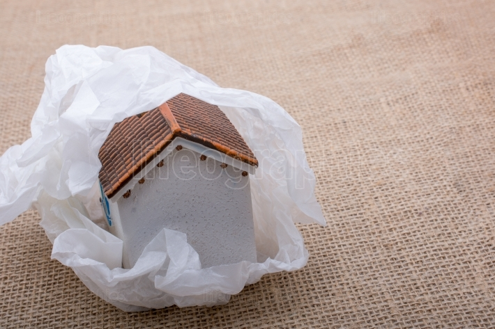 Little model house wrapped in paper