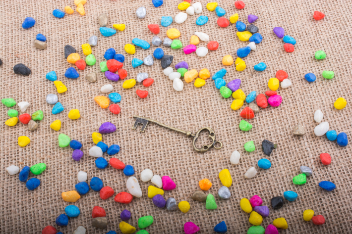 Little retro key amid colorful pebbles