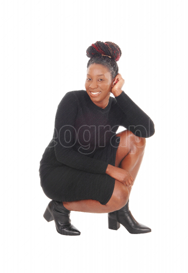 Lovely African woman crouching on floor