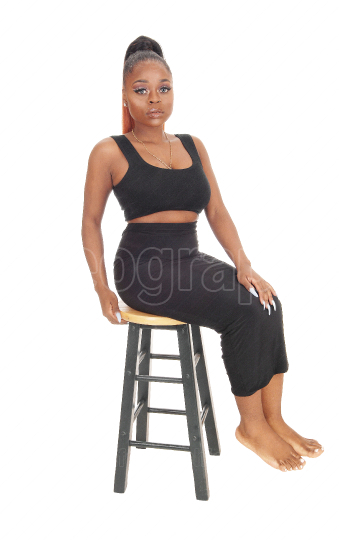 Lovely African woman sitting on a bar chair