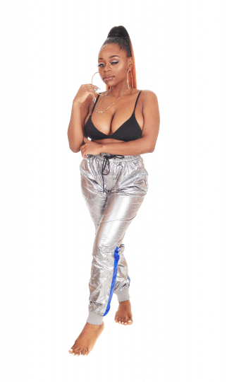 Lovely African woman standing in silver pants and bra