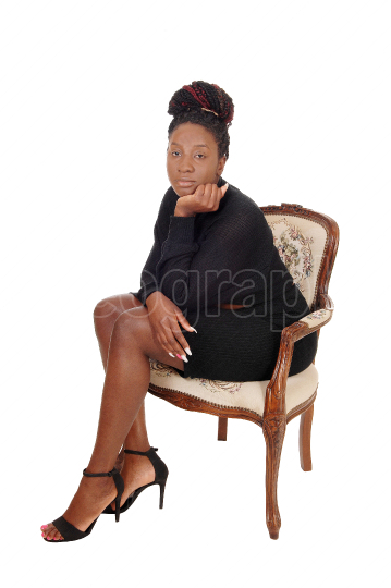 Lovely black female sitting in an old arm chair