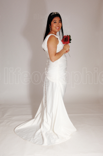 Lovely bride standing in a white gown over gray