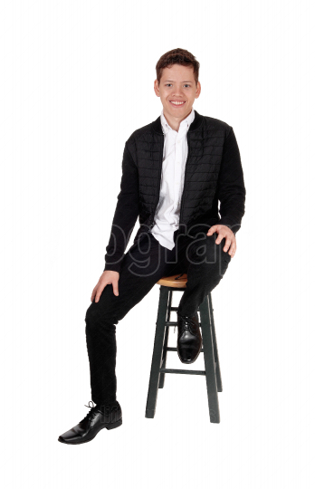 Lovely smiling teenager boy sitting on a chair