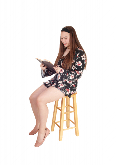 Lovely teenage girl sitting and reading a book