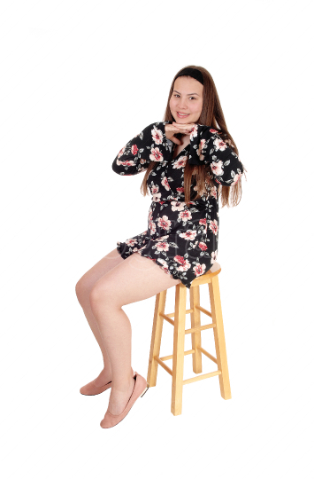Lovely teenage girl sitting on a bar chair, smiling