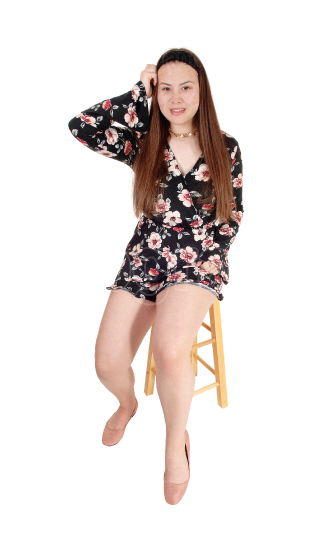 Lovely teenage girl sitting on a chair one hand on head