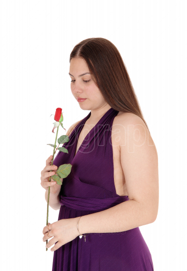 Lovely teenager girl holding a red rose