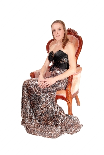 Lovely woman in a long dress sitting in an armchair