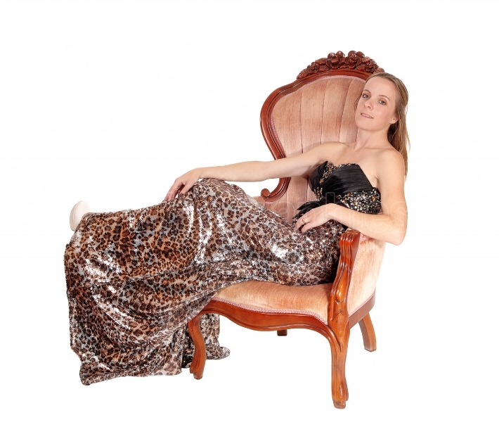 Lovely woman in a long dress sitting in chair