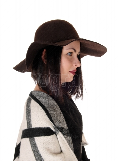 Lovely woman in profile with a hat and poncho