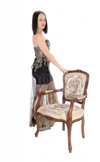 Lovely woman standing with old armchair in dress