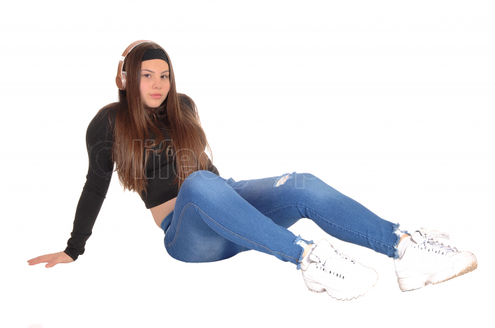 Lovely young teen girl sitting on floor with headphone