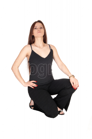 Lovely young woman crouching on the floor in black outfit