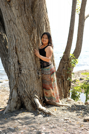 Lovely young woman hugging a big tree