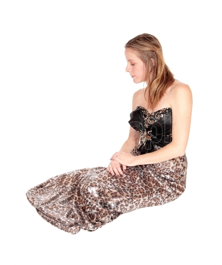 Lovely young woman sitting in a long evening dress