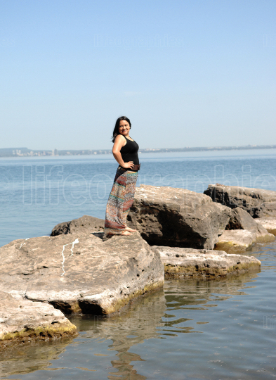 Lovely young woman standing on rocks on the lake Ontario