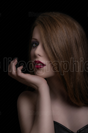 Low key beauty portrait of a sensual woman with red lipstick