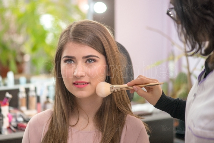 Makeup artist applying makeup to model in salon