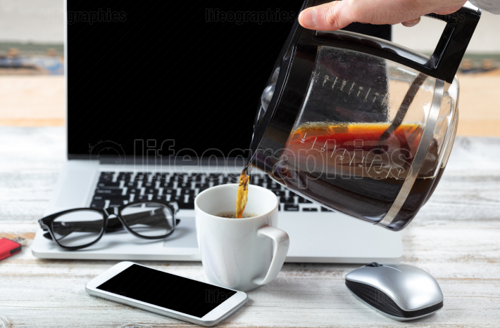 Male hand fulling cup up with coffee with workstation technology