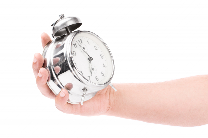 Male hand holding an alarm clock