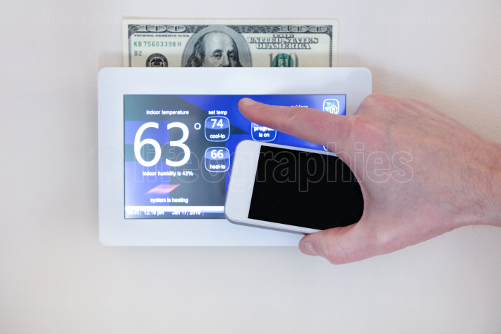 Male hand holding smart phone to operate heating or cooling via