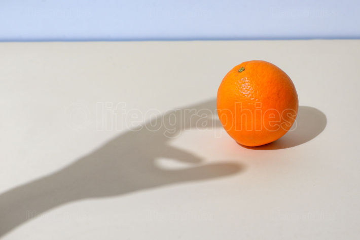 Male hand picks up an orange
